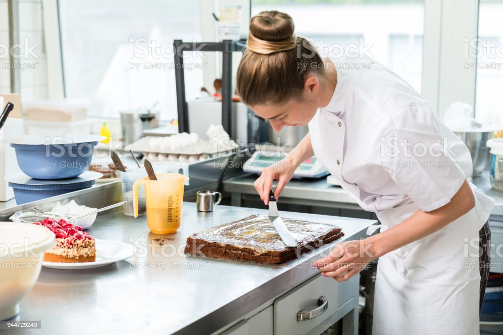Confectioner woman getting chocolate cake ready with topping stock photo