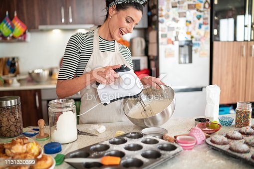 istock Confectioner woman making delicious cream for cupcakes 1131330399