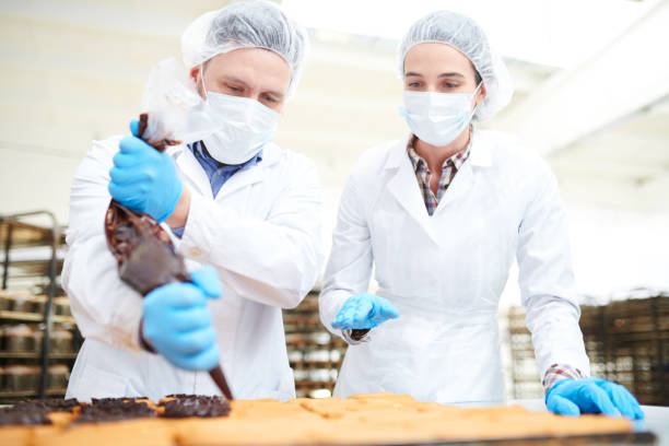 Confectioners pouring chocolate cream from pastry bag Two confectionery factory workers in white coats using icing bag to fill pastry with chocolate cream. hair net stock pictures, royalty-free photos & images