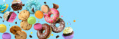 istock Confectionery and sweets collage. Donuts, cupcakes, cookies, macarons flying over blue background. 1278430498