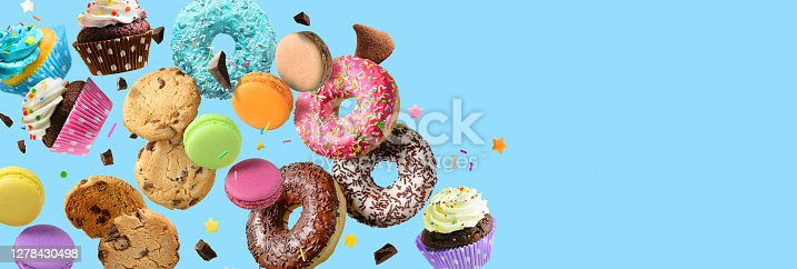 Cakes, sweets, confectionery collage background. Donuts, cookies cupcakes macaroons flying over blue background