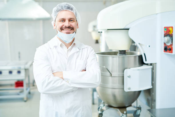 Confectionery factory worker standing and smiling Happy confectionery factory employee standing in white coat with arms crossed and looking at camera. hair net stock pictures, royalty-free photos & images