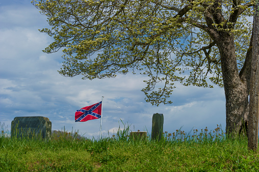 Elizabethton, Tennessee, USA - - April 5, 2020:  An old cemetery on a hill under cloudy skies with a confederate flag fly and a blooming springtime tree.