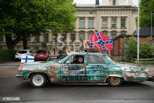 Turku, Finland - June 26, 2015: A car drives through the streets of Turku, Finland, flying a Finnish flag at the front and a Confederate flag on top.