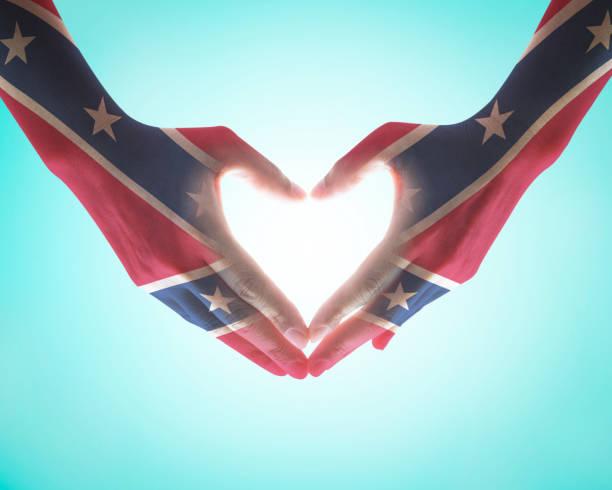 patrón de bandera confederada memorial day en manos del corazón de las personas sobre fondo de cielo azul (trazado de recorte) - feliz dia del policia fotografías e imágenes de stock