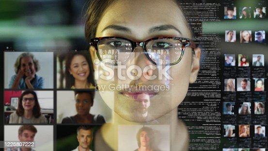 Stock photograph of a professional Asian woman, in her office, looking at a see through display with a team of people making a conference call.