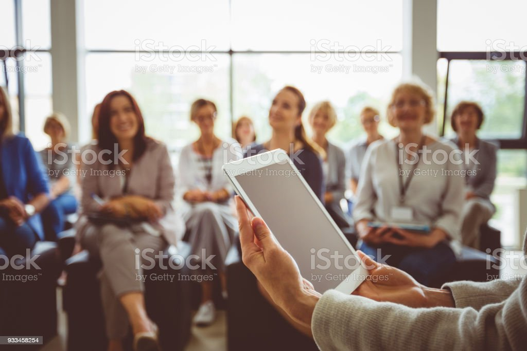 Conference for businesswomen Conference for women. Focus on presenter's hands holding digital tablet. Achievement Stock Photo