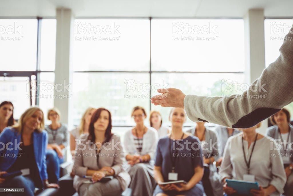 Conference for women Conference for women. Focus on presenter's hand gesturing. Achievement Stock Photo