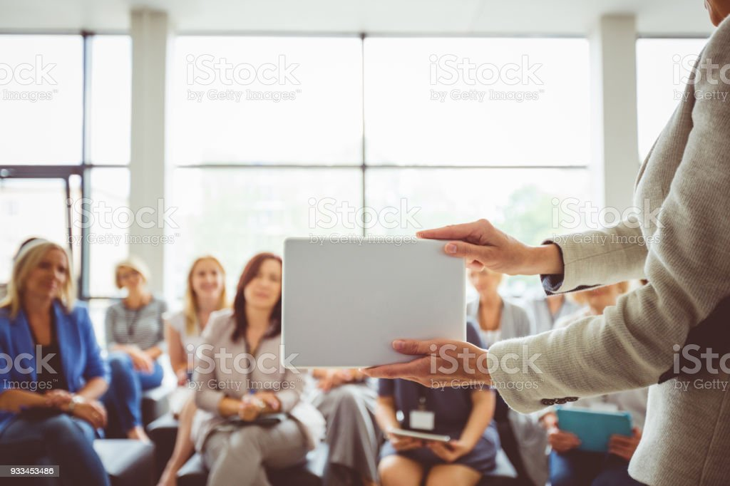 Conference for women Conference for women. Focus on presenter's hands holding digital tablet. Achievement Stock Photo