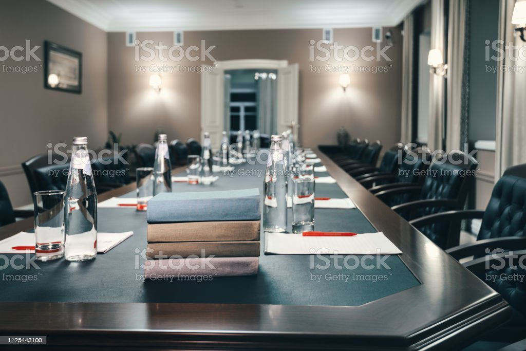 Books in small conference room with a large wooden table. Notebooks...