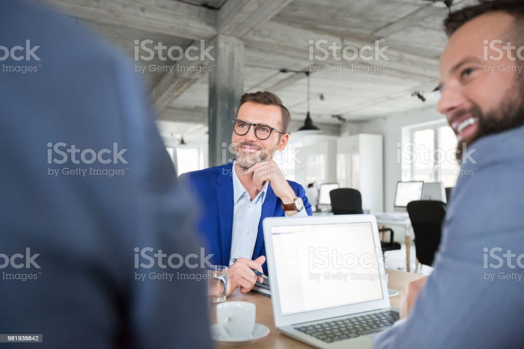 Conference meeting of corporate professionals Mature businessman listening to discussion in meeting room. Conference meeting of corporate professionals. Adult Stock Photo