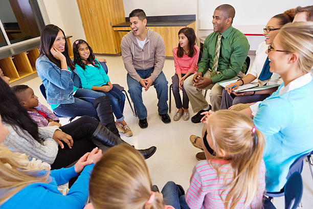 Conference or meeting with elementary school teachers students and parents stock photo
