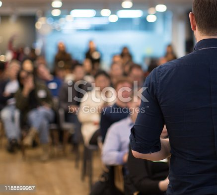 Speaker addressing group. Businessman entrepreneur giving a lecture to a sold-out crowd in a lecture hall. Speaker talking in seminar. Speaker at business conference or presentation stock photo. Male CEO talking during a business presentation in a board room. Copy space. Business coach concept.