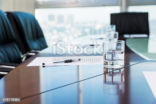 Conference room with blank papers and water glass.