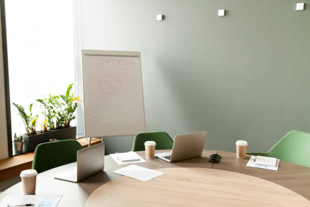 Conference table with laptops in office meeting room with nobody Conference table with laptops and chairs in empty meeting room with nobody, modern company office boardroom interior with flip chart for daily work and corporate team group business briefings concept flipchart stock pictures, royalty-free photos & images