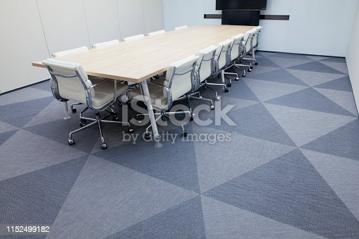 Overhead wide angle perspective view of large bright contemporary modern conference meeting room executive office with teleconference flat LCD screen presentation prepared ready anticipation teamwork group gathering luxury expensive table leather chairs