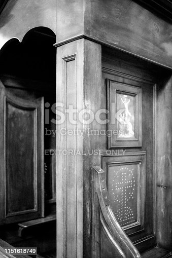 Rome, Italy - April 5, 2019: Black and white image of an old, wooden confessional or confession booth in a catholic church in Rome.
