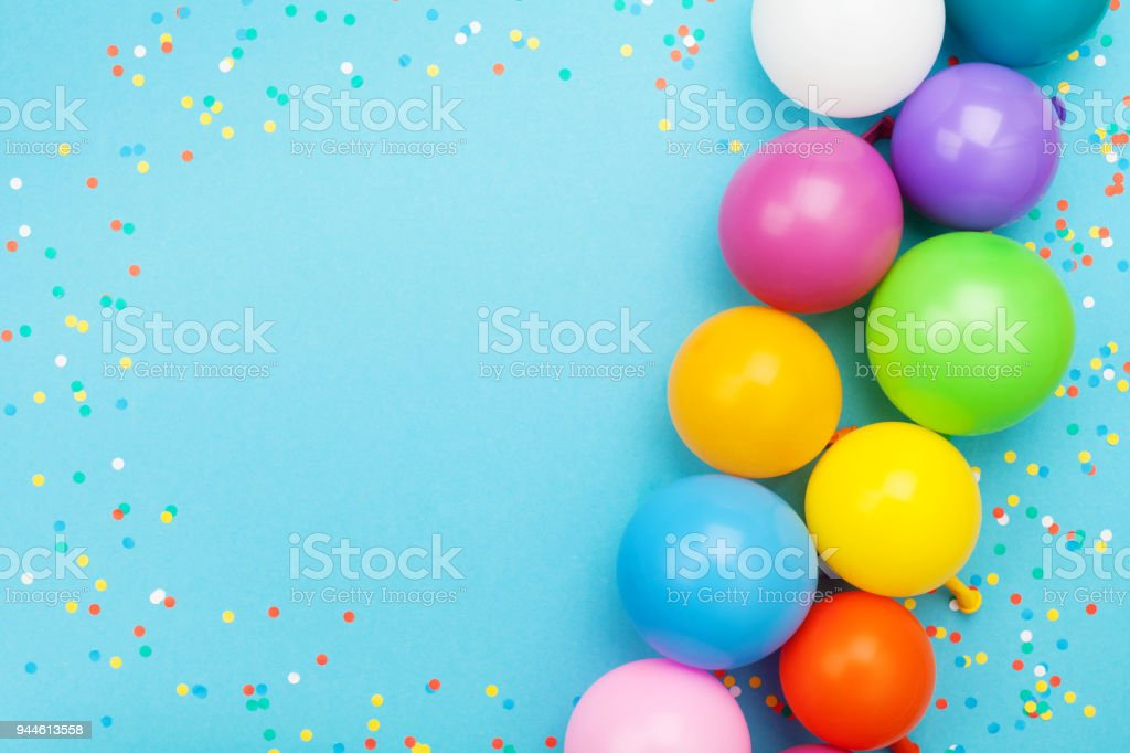 Confetti and colorful balloons for birthday party on blue table top view. Flat lay style. stock photo