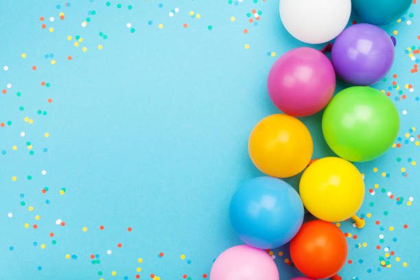 confetti and colorful balloons for birthday party on blue table top view. flat lay style. - happy birthday banner stock photos and pictures
