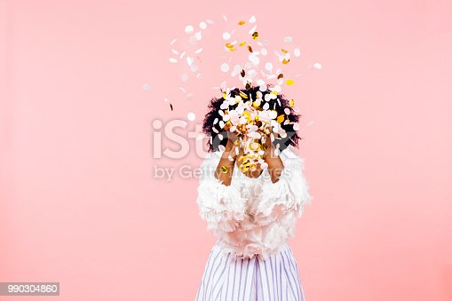 Celebrating happiness, young woman  throwing confetti obscuring her face, isolated on pink background