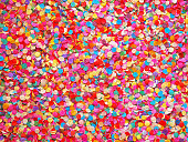 istock Confetti diversity background. Texture colored circles from paper, close-up. Basis for a festive design or a postcard. Carnival, abstract wedding or birthday backdrop 915398636