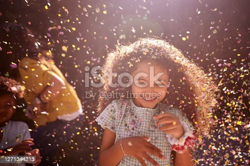 Portrait of confetti falling on little african-american girl with curly hair smiling looking down outdoors