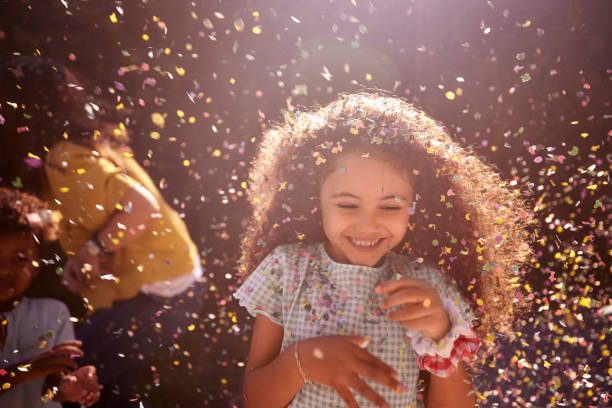 Confetti falling on african-american little girl smiling outdoors stock photo