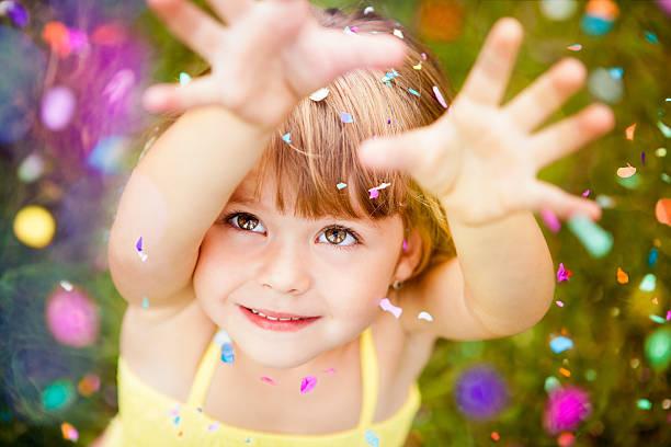 konfetti fallen auf kleine mädchen - kinderparty spiele stock-fotos und bilder