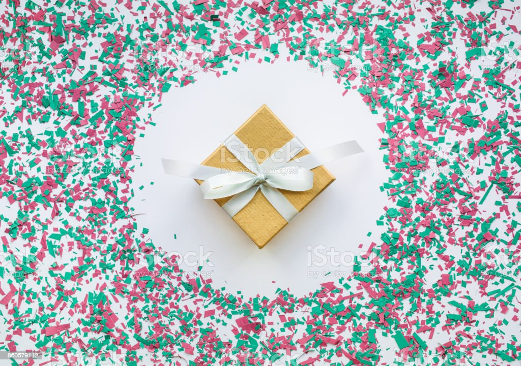 Confetti in christmas decoration color with gift box on white stock photo