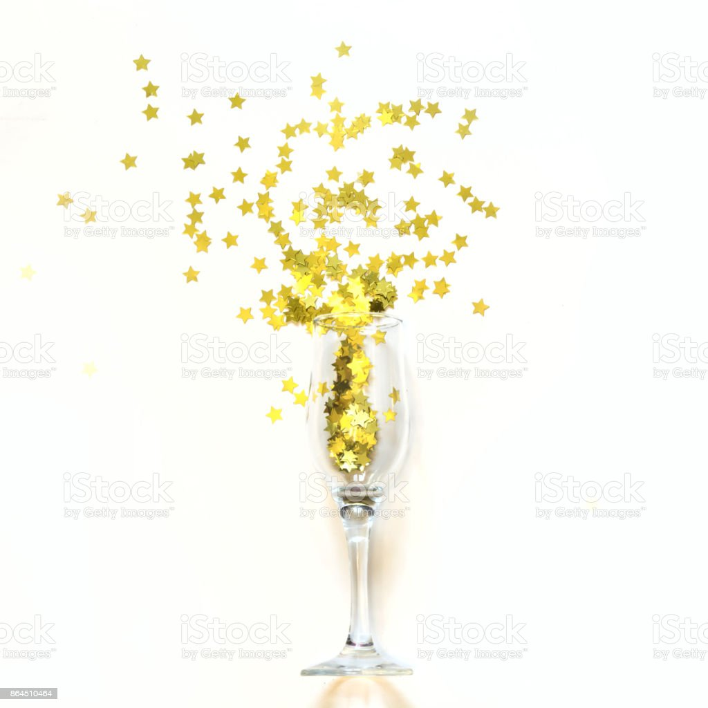 Confetti in the shape of stars poured out glasses of champagne on the white background. stock photo