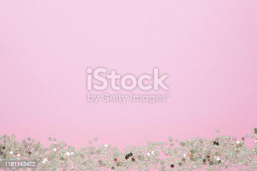 1040055260istockphoto Confetti of gold stars glisten on a pink background. Festive holiday pastel backdrop. 1181143422