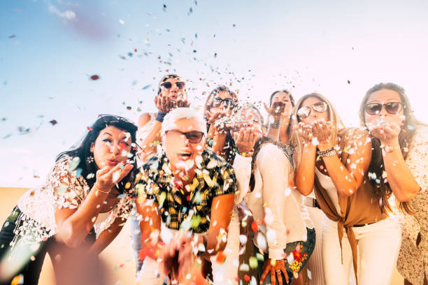 Confetti party celebration for happy cheerful crazy caucasian people women blowing out enjoying the event outdoor - carnival or birthday concept for cheerful pretty ladies stock photo