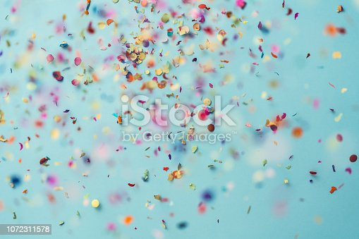 Confetti rain on blue background. Directly above shot.