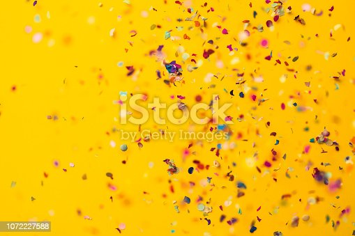 Confetti rain on yellow background. Directly above shot.