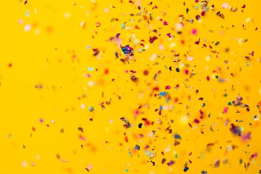 Confetti rain on yellow background. Directly above shot.