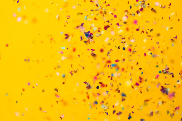 confetti rain on yellow background - celebration stock pictures, royalty-free photos & images