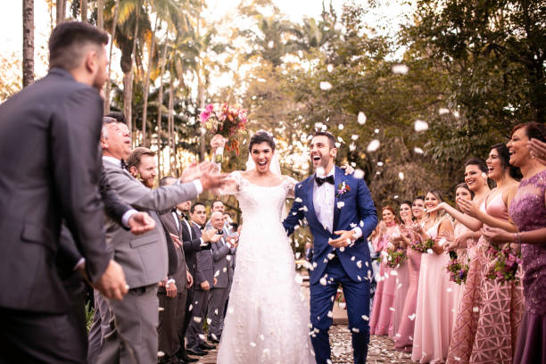 Confetti throwing on happy newlywed couple stock photo