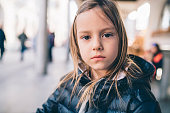Cute young girl portrait in the city. She is wearing warm clothing and she is looking at camera with serious expression on her face.
