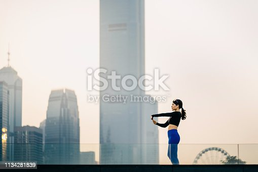 Confidence and determined Asian sports woman stretching arms outdoors against urban cityscape at sunset