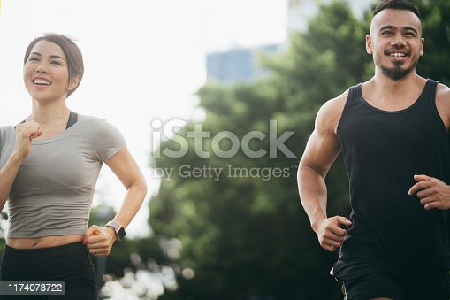 Confidence and energetic young sporty couple going for a run outdoors at city park in the morning
