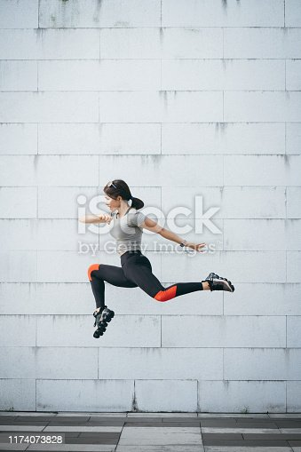 Confidence and energetic young sporty woman jumping in air against grey wall at city park