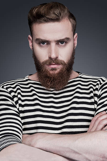 Confidence and masculinity. Confident young bearded man in striped clothing keeping arms crossed and looking at camera while standing against grey background sailor suit stock pictures, royalty-free photos & images