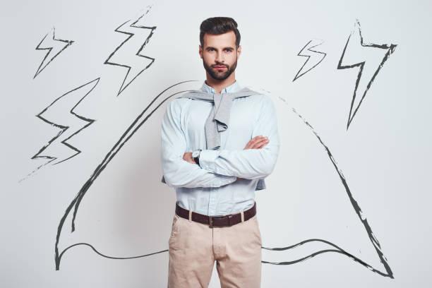 confiança e poder. o homem farpado charming que desgasta um cabo desenhado com braços cruzados está olhando a câmera ao estar de encontro ao fundo cinzento com ilustração dos parafusos de relâmpago - capuz - fotografias e filmes do acervo