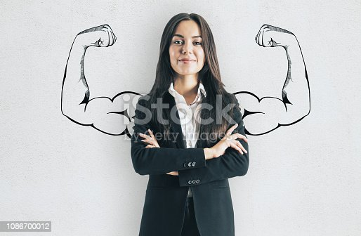 Portrait of attractive young european businesswoman with drawn muscly arms. Confidence and strength concept