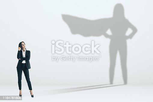 Pretty businesswoman with superhero shadow on concrete wall background. Confidence and success concept