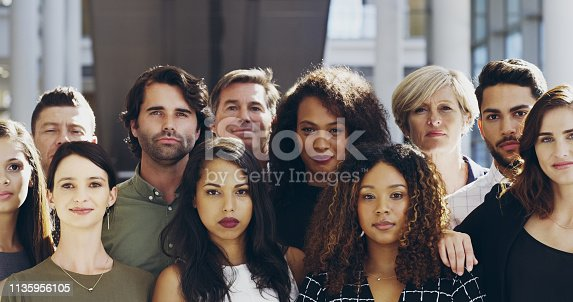 Cropped shot of a group of businesspeople standing in their workplace