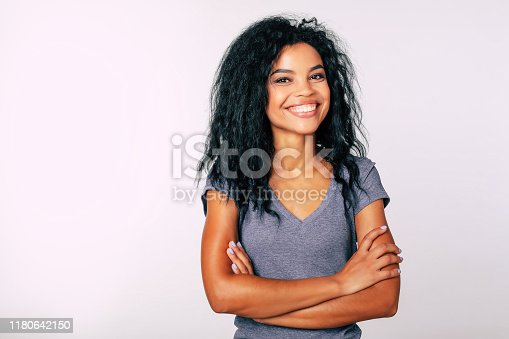 910856488 istock photo Confidence, as it is. Close-up photo of young African American woman with medium-length wavy dark hair standing with folded arms looking at the camera and smiling broadly. 1180642150