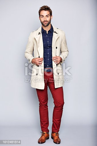 Studio portrait of a handsome young man posing in a trench coat against a grey background