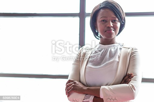 Young female business executive standing arm crossed near a large bright window in her office.