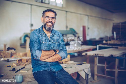 Carpenter in wood workshop. Mature man in casual clothing. Space is full of working tools and wooden planks.